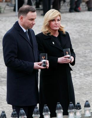 Croatia's President Kolinda Grabar-Kitarovic, right, and Polish President Andrzej Duda hold candles during a ceremony at the former Auschwitz Nazi death camp in Oswiecim, Poland, Wednesday, Jan. 27, 2016, on  the 71st anniversary of the death camp's liberation by the Soviet Red Army in 1945. (AP Photo/Czarek Sokolowski)