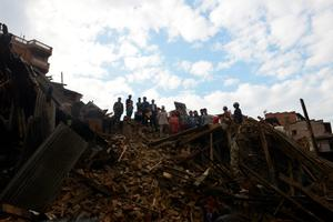 "Residents look on from the top of collapsed houses in Bhaktapur, on the outskirts of Kathmandu, on April 27, 2015, two days after a 7.8 magnitude earthquake hit Nepal. Nepalis started fleeing their devastated capital on April 27 after an earthquake killed more than 3,800 people and toppled entire streets, as the United Nations prepared a ""massive"" aid operation.  AFP PHOTO / PRAKASH MATHEMAPRAKASH MATHEMA/AFP/Getty Images"