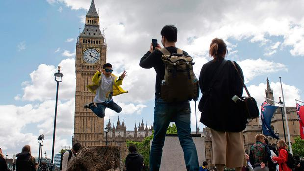 TOPSHOT - Tourists gather near the Elizabeth Tower, commonly referred to as Big Ben, at the Houses of Parliament in central London on June 7, 2017, on the eve of the general election. Britain on Wednesday headed into the final day of campaigning for a general election darkened and dominated by jihadist attacks in two cities, leaving forecasters struggling to predict an outcome on polling day. / AFP PHOTO / Justin TALLISJUSTIN TALLIS/AFP/Getty Images