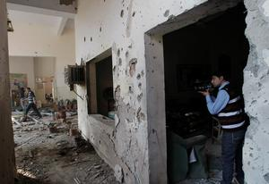 A Pakistani journalist films inside the Army Public School attacked the day before by Taliban gunmen in Peshawar, Pakistan, Wednesday, Dec. 17, 2014. Pakistan mourned as the nation prepares for mass funerals Wednesday for over 140 people, most of them children, killed in the Taliban massacre in the military-run school in the country's northwest in the deadliest and most horrific attacks in years, officials said. (AP Photo/Mohammad Sajjad)