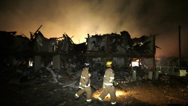 Firefighters check a destroyed apartment complex near the fertilizer plant that exploded earlier in West, Texas, in this photo made early Thursday, April 18, 2013.  (AP Photo/LM Otero)