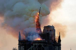 The steeple of the landmark Notre-Dame Cathedral collapses as the cathedral is engulfed in flames in central Paris on April 15, 2019. - A huge fire swept through the roof of the famed Notre-Dame Cathedral in central Paris on April 15, 2019, sending flames and huge clouds of grey smoke billowing into the sky. The flames and smoke plumed from the spire and roof of the gothic cathedral, visited by millions of people a year. A spokesman for the cathedral told AFP that the wooden structure supporting the roof was being gutted by the blaze. (Photo by Geoffroy VAN DER HASSELT / AFP)        (Photo credit should read GEOFFROY VAN DER HASSELT/AFP/Getty Images) *** BESTPIX ***