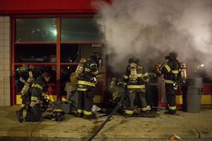 DELLWOOD, MO - NOVEMBER 25:  Firemen extinguish a burning business during rioting on November 25, 2014 in Dellwood, Missouri. Ferguson has been struggling to return to normal after Brown, an 18-year-old black man, was killed by Darren Wilson, a white Ferguson police officer, on August 9. His death has sparked months of sometimes violent protests in Ferguson. A grand jury today declined to indict officer Wilson.  (Photo by Aaron P. Bernstein/Getty Images)