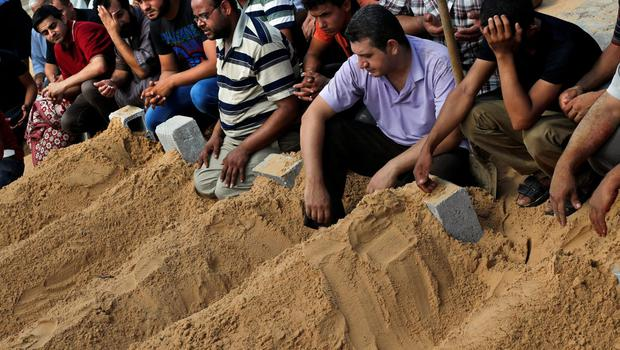 Mourners pray over the fresh graves of members of the Abu Jarad family who were killed in an Israeli strike on their family house, following their funerals in Beit Lahiya, in the northern Gaza Strip, Saturday, July 19, 2014. (AP Photo/Lefteris Pitarakis)