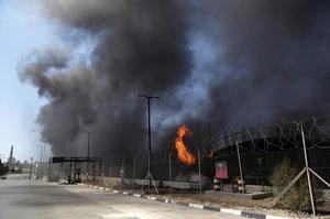 Smoke and flames rise from the Gaza power plant after it was hit by Israeli strikes, in the Nusseirat refugee camp, central Gaza Strip,Tuesday, July 29, 2014. (AP Photo/Adel Hana)