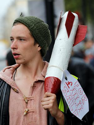 A demonstrator carries a fake bomb made of paper during a protest against the visit of Israel's Prime Minister Benjamin Netanyahu to Britain, in front of Downing Street in London, Wednesday, Sept. 9, 2015. (AP Photo/Frank Augstein)