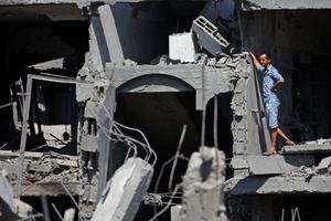 A Palestinian inspects a destroyed house, in the heavily bombed town of Beit Hanoun, Gaza Strip, close to the Israeli border, Friday, Aug. 1, 2014.  (AP Photo/Lefteris Pitarakis)