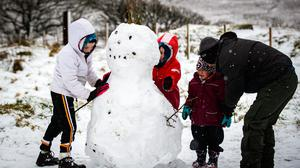 The Clarke and Slane family build a snowman on the hills of Belfast on December 27th 2020 (Photo by Kevin Scott for Belfast Telegraph)