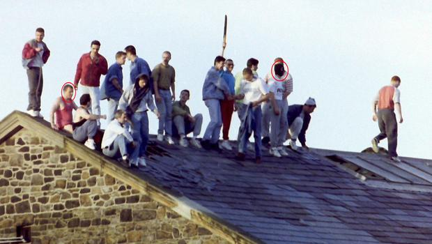 1994 Loyalist roof top protest at Crumlin Road prison - Dee Stitt in black  balaclava, white t-shirt and grey track bottoms. Johnny Adair pink vest top