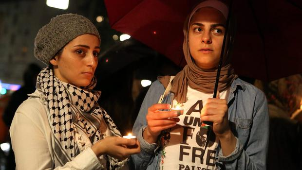 Demonstrators hold candles in the rain during a memorial vigil of those killed during the continued violence in Gaza, on July 24, 2014 in Berlin, Germany. (Photo by Adam Berry/Getty Images)