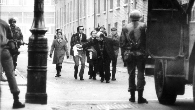 Father Edward Daly uses a blood-stained handkerchief as a white flag on Bloody Sunday in 1972