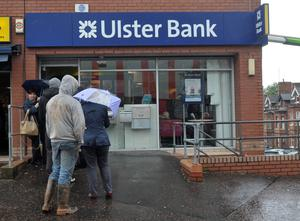 Customers queuing at a branch in north Belfast. Northern Ireland's big four banks have closed 77 branches in the last four years
