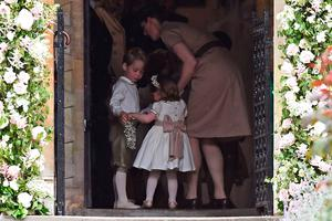ENGLEFIELD GREEN, ENGLAND - MAY 20: Britain's prince George (L), a pageboy, Britain's princess Charlotte, a bridesmaid, stand with their nanny Maria Borrallo, as they attend the wedding of their aunt Pippa Middleton to James Matthews at St Mark's Church on May 20, 2017 in Englefield Green, England.  (Photo by Justin Tallis - WPA Pool)