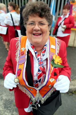 An Orangewoman from Glasgow, poses for a photograph as the main 12th July parade moves off from Carlisle circus in Belfast, on July 12, 2016. 12th July is the main marching day in the Orange Order calendar. The parades mark the 326th anniversary of King William III's victory at the Battle of the Boyne in 1690. / AFP PHOTO / PAUL FAITHPAUL FAITH/AFP/Getty Images