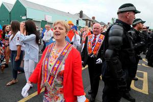 The parade marches past police, keeping Nationalist protestors away from a Loyalist feeder parade, passing the Nationalist Ardoyne shops on its way to join the main 12th July celebrations on July 12, 2016, the return parade has been banned from returning passed the shops this evening. 12th July is the main marching day in the Orange Order calendar. The parades mark the 326th anniversary of King William III's victory at the Battle of the Boyne in 1690. / AFP PHOTO / PAUL FAITHPAUL FAITH/AFP/Getty Images