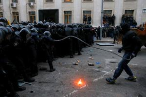 A protester uses a chain as he and others clash with police outside of the presidential administration building in downtown Kiev, Ukraine, on Sunday, Dec. 1, 2013. More than 100,000 demonstrators chased away police to rally in the center of Ukraine's capital on Sunday. Thousands of demonstrators tried to storm the nearby presidential administration building, but were driven back by riot police using tear gas and flash grenades, which produce a loud bang but are not intended to cause injury. The standoff continued, with more demonstrators arriving. (AP Photo/Sergei Grits)
