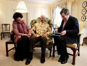 File photo dated 02/02/05 of Chancellor of the Exchequer Gordon Brown (right) being given a photograph of his visit to South Africa last year, during a meeting with former South African President Nelson Mandela and his wife, Graca Machel. Former South African leader Nelson Mandela has died at the age of 95, the country's president, Jacob Zuma, said tonight. PRESS ASSOCIATION Photo. Issue date: Thursday December 5, 2013. See PA story DEATH Mandela. Photo credit should read Stephen Hird/PA Wire
