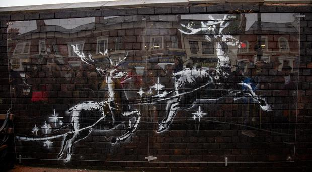 A Banksy mural in Birmingham has been protected with a sheet of perspex after a mystery artist made an overnight addition (Jacob King/PA)
