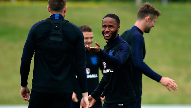 Raheem Sterling chats with Phil Jones during a training session at St George's Park.