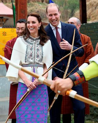 THIMPHU, BHUTAN - APRIL 14:  Prince William, Duke of Cambridge fires an arrow as Catherine, Duchess of Cambridge looks on during an Bhutanese archery demonstration on the first day of a two day visit to Bhutan on the 14th April 2016 in Paro, Bhutan. The Royal couple are visiting Bhutan as part of a week long visit to India and Bhutan that has taken in cities such as Mumbai, Delhi, Kaziranga, Bhutan and Agra.  (Photo by Chris Jackson/Getty Images)