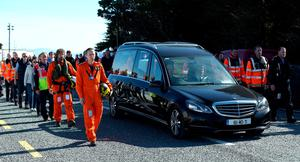 The body of Captain Mark Duffy is driven in a hearse along the seafront accompanied by a guard of honour at Blacksod Co. Mayo, Ireland, recovered from the wreckage of an Irish Coast Guard helicopter that crashed in the Atlantic.
