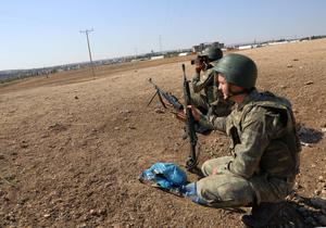 Turkish soldiers take positions, a few hundreds meters from the border line as fighting intensifis between Syrian Kurds and the militants of Islamic State, in Kobani in Syria, in the background, in Mursitpinar near Suruc, Turkey, Saturday, Oct. 4, 2014. Turkey's parliament approved Thursday a motion that gives the government new powers to launch military incursions into Syria and Iraq and to allow foreign forces to use its territory for possible operations against the Islamic State group. (AP Photo/Burhan Ozbilici)