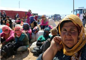 Syrian Kurdish women wait for transport as thousands of new Syrian refugees from Kobani arrive at the Turkey-Syria border  crossing of Yumurtalik near Suruc, Turkey, Wednesday, Oct. 1, 2014. U.S.-led coalition airstrikes targeted Islamic State fighters pressing their offensive against a Kurdish town near the Syrian-Turkish border on Tuesday in an attempt to halt the militants' advance, activists said.(AP Photo/Burhan Ozbilici)