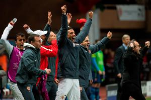 Monaco's substitute players and staff members celebrate at the final whistle of the UEFA Champions League football match Monaco vs Arsenal, on March 17, 2015 at Louis II stadium in Monaco. AFP PHOTO / BERTRAND LANGLOISBERTRAND LANGLOIS/AFP/Getty Images
