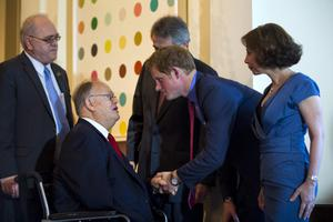 WASHINGTON, DC - MAY 09:  HRH Prince Harry (C) and Lady Westmacott (R) greet former Democratic Senator from Georgia Max Cleland (L) at a dinner at the British Ambassador's residence on May 9, 2013 in Washington, DC. (Photo by Jim Lo Scalzo - Pool/ Getty Images)