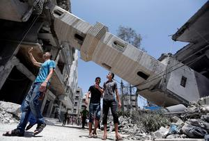 Palestinians inspect damage to adjacent houses from a fallen minaret of the Al-Sousi mosque that was destroyed in an Israel strike, at the Shati refugee camp, in the northern Gaza Strip, Wednesday, July 30, 2014. (AP Photo/Lefteris Pitarakis)