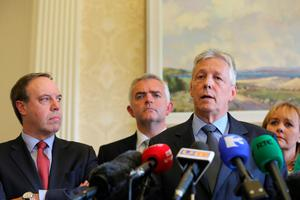 First Minister Peter Robinson at Stormont, Belfast, watched by Nigel Dodds, Johnathan Bell  and Michelle Mcilveen,  announces that he is standing aside, and the majority of his Democratic Unionist ministers are to resign, with party colleague Arlene Foster to take over as acting First Minister. PRESS ASSOCIATION Photo. Picture date: Thursday September 10, 2015. The surprise move from the DUP leader comes amid an Assembly crisis in the wake of a murder linked to the IRA murder. See PA story ULSTER Politics. Photo credit should read: Niall Carson/PA Wire