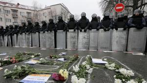 Flowers from pro-European union activists lay in front of police outside the Presidential office in Kiev, Ukraine, Sunday, Dec. 8, 2013, with various messages supporting their cause.   Thousands of Ukrainians angered by police violence and the president's turn away from Europe are expected to converge on the capital Sunday. (AP Photo/Efrem Lukatsky)