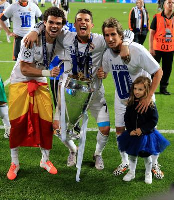 Real Madrid's Pepe (left), Cristiano Ronaldo (centre) and Fabio Coentrao celebrate with the UEFA Champions League Trophy after the UEFA Champions League Final at at the Estadio da Luiz, Lisbon, Portugal. PRESS ASSOCIATION Photo. Picture date: Saturday May 24, 2014. See PA story SOCCER Final. Photo credit should read: Nick Potts/PA Wire. RESTRICTIONS: Editorial use only. No commercial use. No video emulation. No false commercial association.