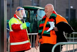 Fans have their tickets checked by security staff wearing PPE ahead of the Sadler's Peaky Blinders Irish Cup Final match at Windsor Park, Belfast. PA Photo. Picture date: Friday July 31, 2020. Friday's Irish Cup final between Ballymena United and Glentoran is the first football match in the UK to be played in front of spectators since March. Photo credit should read: Liam McBurney/PA Wire