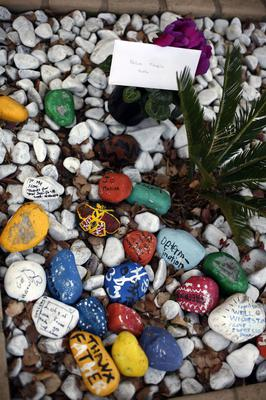 A flower pot with and stones painted and covered in graffiti wishing former South African President Nelson Mandela prompt recovery were set outside his Johannesburg home Monday, June 10, 2013. (AP Photo/Jerome Delay)
