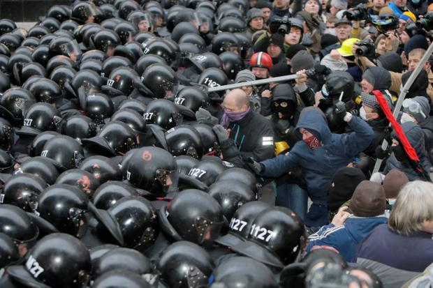 Protesters clash with police at Presidential office in Kiev, Ukraine, on Sunday, Dec. 1, 2013. As many as 100,000 demonstrators chased away police to rally in the center of Ukraine's capital on Sunday, defying a government ban on protests on Independence Square, in the biggest show of anger over the president's refusal to sign an agreement with the European Union. (AP Photo/Efrem Lukatsky)