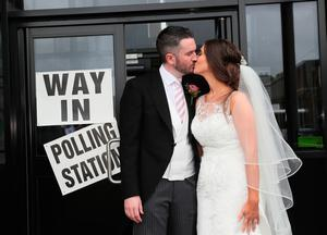 Alliance candidate for West Belfast Sorcha Eastwood casts her vote in the 2017 General Election, with her husband, Dale Shirlow, at a polling station in Lisburn, Northern Ireland, still wearing her wedding dress after they were married earlier in the day. Brian Lawless/PA Wire
