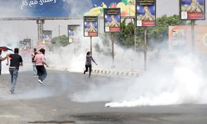 Palestinian protesters run from tear gas thrown by Israeli soldiers during a demonstration against the Israeli military action in Gaza, near the West Bank city of Nablus, Tuesday, July 22, 2014. (AP Photo/Nasser Ishtayeh)