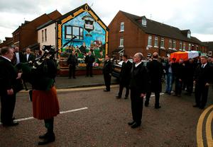 """Mourners pause with the coffin of Gerard """"Jock"""" Davison, a former IRA commander, at the site of his shooting in the Market's Area of Belfast."""