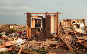 MOORE, OK- MAY 20:  Dana Ulepich searches inside a room left standing at the back of her house destroyed after a powerful tornado ripped through the area on May 20, 2013 in Moore, Oklahoma. The tornado, reported to be at least EF4 strength and two miles wide, touched down in the Oklahoma City area on Monday killing at least 51 people. (Photo by Brett Deering/Getty Images)