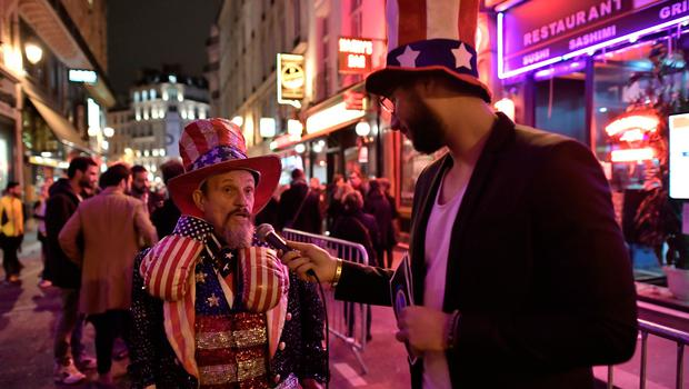 "A man, dressed in colours of the US national flag, speaks to a journalist outside the Harry's New York Bar in Paris on November 8, 2016 where a straw vote for US citizens living in France has been organized for the US Presidential elections.  Expatriate Americans monitor the US election returns at Harry's New York Bar in Paris, which prides itself on having correctly predicted the outcome of US elections all but twice since launching its traditional ""straw poll"" in 1924. / AFP PHOTO / PHILIPPE LOPEZPHILIPPE LOPEZ/AFP/Getty Images"