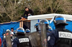 "A man on a shelter's roof refusing to leave speaks with anti-riot policemen as agents dismantle shelters on February 29, 2016 in the ""jungle"" migrants and refugees camp in Calais, northern France.  A French court on February 25 gave the green light to plans to evacuate hundreds of migrants from the southern half of the sprawling camp in the port town, with many wanting to stay near the entrance to the Channel Tunnel, the gateway to their ultimate goal of Britain. AFP PHOTO / PHILIPPE HUGUENPHILIPPE HUGUEN/AFP/Getty Images"