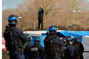 "A man on a shelter's roof refusing to leave gestures in front of anti-riot policemen as agents dismantle shelters on February 29, 2016 in the ""jungle"" migrants and refugees camp in Calais, northern France.  A French court on February 25 gave the green light to plans to evacuate hundreds of migrants from the southern half of the sprawling camp in the port town, with many wanting to stay near the entrance to the Channel Tunnel, the gateway to their ultimate goal of Britain. AFP PHOTO / PHILIPPE HUGUENPHILIPPE HUGUEN/AFP/Getty Images"