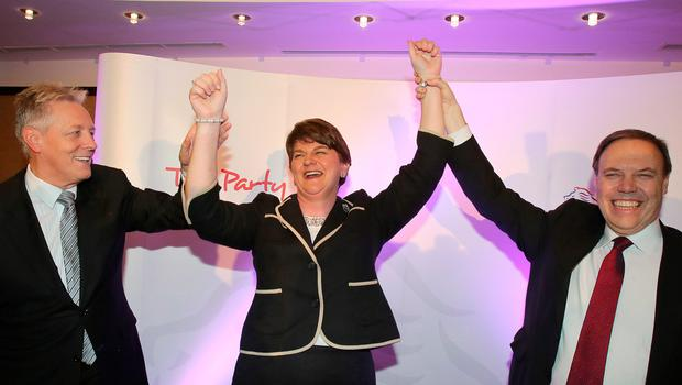 Former DUP leader Peter Robinson (L) and deputy leader Nigel Dodds (R) raise their hands with new leader Arlene Foster, Northern Ireland Finance Minister in Belfast after being elected leader of the Democratic Unionist Party (DUP) on December 17, 2015. A special electoral college will gather at the hotel, and Foster is the only candidate for the leadership. Foster will replace Peter Robinson following his announcement that he will step down as Northern Ireland's First Minister and as leader of the DUP.  AFP PHOTO / PAUL FAITHPAUL FAITH/AFP/Getty Images