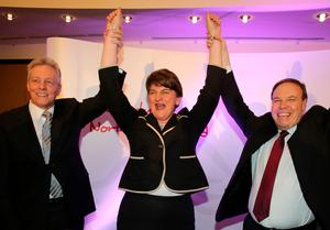 Former DUP leader Peter Robinson (L) and deputy leader Nigel Dodds (R) raise the arms of new leader Arlene Foster, Northern Ireland Finance Minister in Belfast after being elected leader of the Democratic Unionist Party (DUP) on December 17, 2015. A special electoral college will gather at the hotel, and Foster is the only candidate for the leadership. Foster will replace Peter Robinson following his announcement that he will step down as Northern Ireland's First Minister and as leader of the DUP.  AFP PHOTO / PAUL FAITHPAUL FAITH/AFP/Getty Images