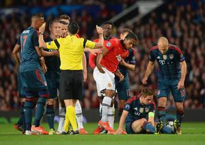 MANCHESTER, ENGLAND - APRIL 01:  Referee Carlos Velasco Carballo shows Luis Antonio Valencia of Manchester United a yellow card for a foul on Philipp Lahm of Bayern Muenchen during the UEFA Champions League Quarter Final first leg match between Manchester United and FC Bayern Muenchen at Old Trafford on April 1, 2014 in Manchester, England.  (Photo by Michael Regan/Bongarts/Getty Images)