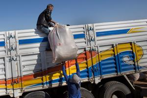 SANLIURFA, TURKEY - OCTOBER 01:  A man lifts a sack on a truck full of refugees after they had crossed the border from Syria into Turkey on October 1 , 2014 near Suruc, Turkey. Kurdish troops are engaged in a battle against fighters of the Islamic State (IS, also called ISIS and ISIL) to defend the strategic nearby Kurdish border town of Kobani (also called Ayn Al-Arab), which ISIS has surrounded on three sides. The Turkish Parliament is due to vote on a measure on October 2, which would allow Turkish ground forces to enter Syria, creating a buffer zone to protect fleeing refugees from the ISIS advance.  (Photo by Carsten Koall/Getty Images)