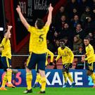 On target: Arsenal's striker Bukayo Saka (centre) celebrates with team-mates after scoring the Gunners' opening goal last night against Bournemouth