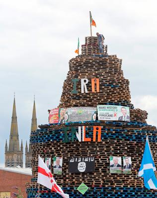Posters of Sinn Fein politicians are seen placed on a bonfire in Shankill. [Photo: Paul Faith/AFP/Getty Images]