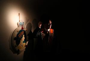 A member of the Orange Order poses beside a portrait of Queen Elizabeth II ahead of an Orange Order parade in  Belfast, as part of the annual Twelfth of July celebrations, marking the victory of King William III's victory over James II at the Battle of the Boyne in 1690. PRESS ASSOCIATION Photo. Picture date: Friday July 12, 2019. See PA story ULSTER Twelfth. Photo credit should read: Brian Lawless/PA Wire